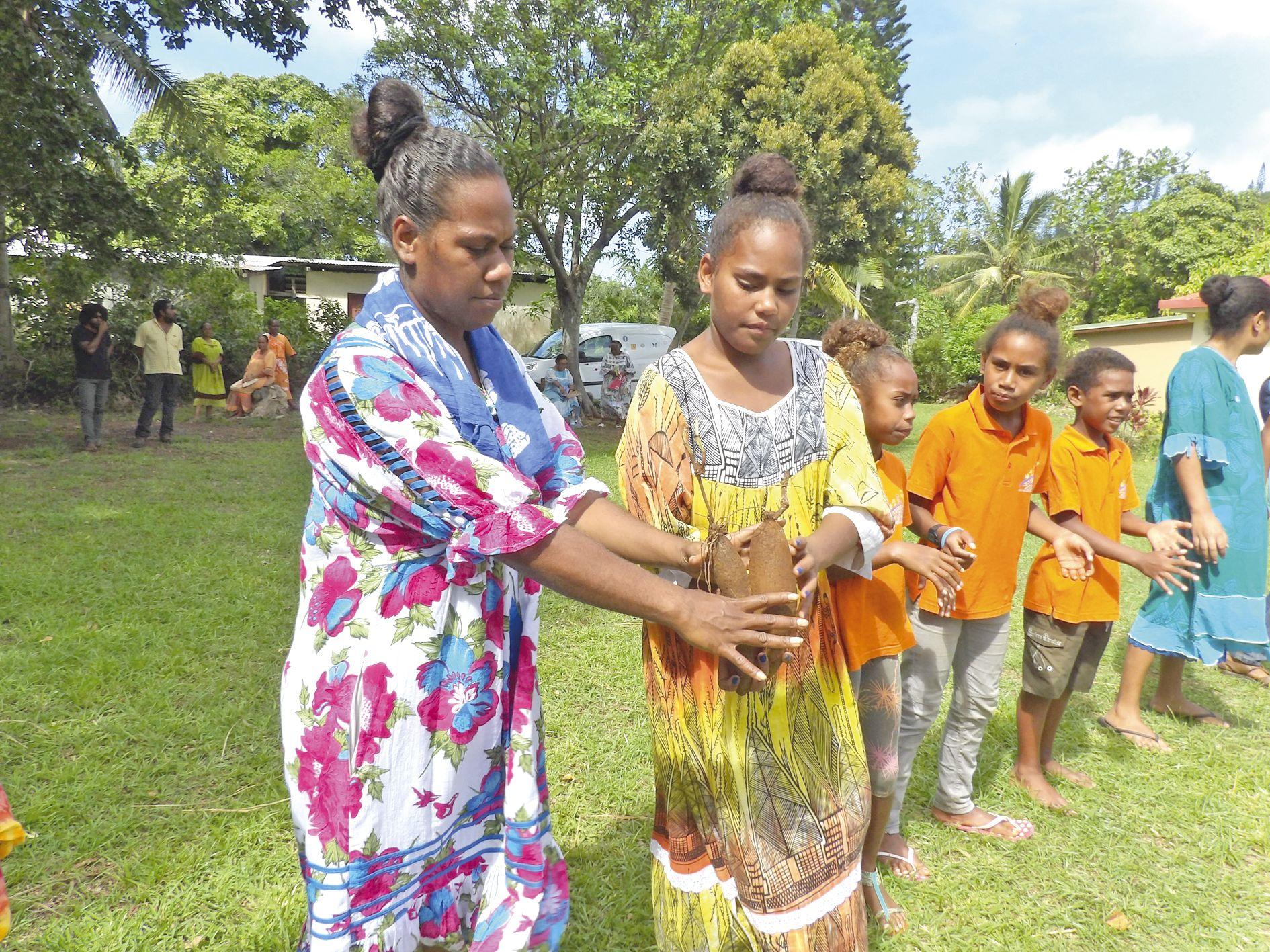 Après la bénédiction des ignames en l'église, les enfants ont réalisé une chaîne humaine pour recomposer le tas de tubercules, mis en ordre uniquement par les hommes.