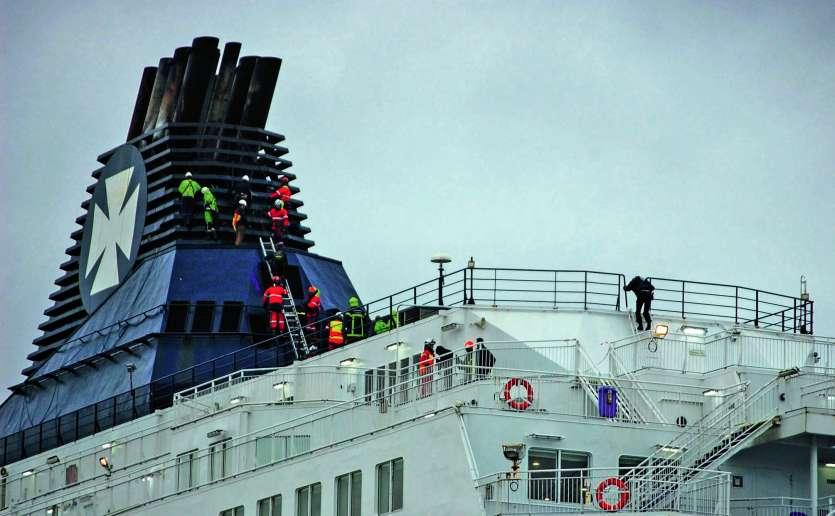 Les sapeurs-pompiers du Grimp (Groupe de reconnaissance et d'intervention en milieu périlleux) tentant de faire descendre les migrants du haut de la cheminée du ferry Calais seaways, qui venait d'arriver de Douvres, en Angleterre.Photo Bernard Barron/AFP