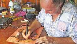 La pyrogravure constitue la première étape de Bruno Curet, (ici dans son atelier à Tahiti) qui y revient cependant plusieurs fois au cours de son processus de création.