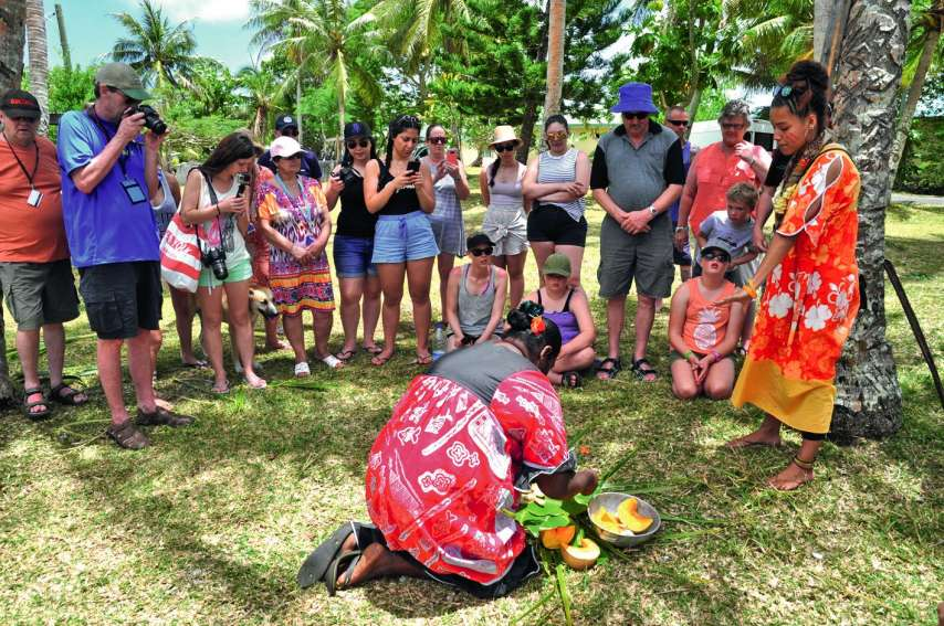 Salomé (en robe orange) explique aux touristes la confection d'un bougna à base de lait de coco fraîchement râpé, refermé dans des feuilles de bananier par une maman de la tribu. Photos SM
