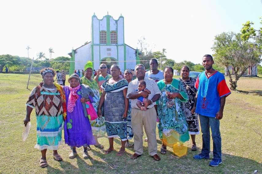 Le pasteur Seiko Wamejo, portant son petit-fils, et quelques paroissiens de Xépénéhé et de Siloam devant le temple de Xépénéhé après sa dernière messe. L'homme de foi a pris son dernier petit-déjeuner à la maison commune de Xépénéhé avec ses fidèles avant