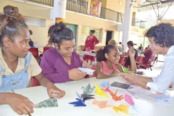 Marie M. apprend l'origami  aux jeunes avant son spectacle