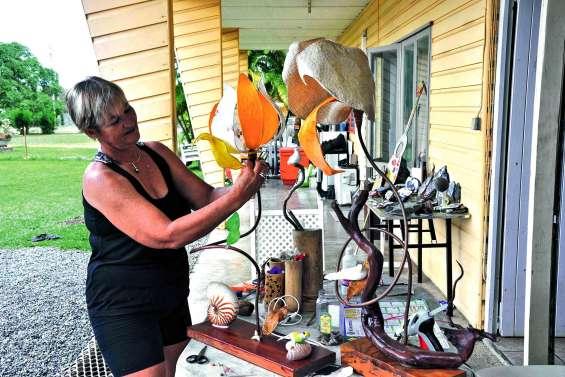 Muriel Song entre lampes  et peintures sur cailloux