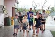 Raquettes et balles jaunes en main, durant l'été, au tennis club